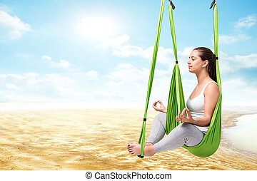 Woman doing aero yoga against seamless landscape.