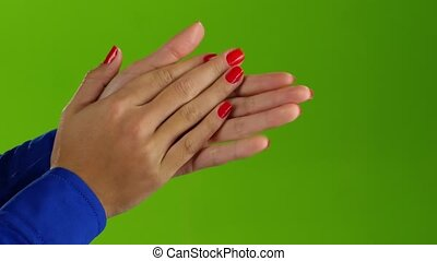 Woman doing applause her hands on a green screen background...