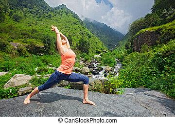 Woman doing Ashtanga Vinyasa Yoga asana Virabhadrasana 1 Warrior
