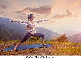 Woman doing Ashtanga Vinyasa Yoga asana Virabhadrasana 2 Warrior