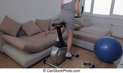 Woman doing cardio on stationary bicycle