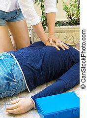 Woman doing cardiopulmonary resuscitation to a man.