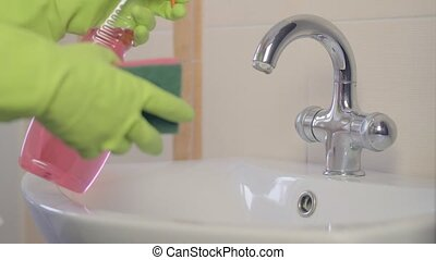woman doing chores in bathroom at home, cleaning sink and faucet with spray detergent. Sequence