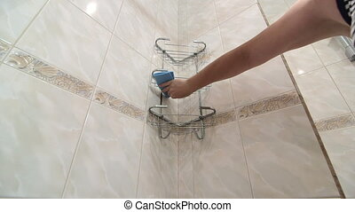 Woman doing chores in bathroom cleaning shower room shelf