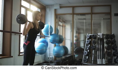 Woman doing classic squats with a barbell standing up, in a sports club.