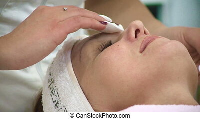 Woman doing cosmetic procedures in spa clinic.