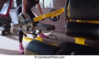 Fitness woman doing deadlift on a exercise machine in the gym