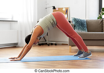 woman does downwardfacing dog yoga pose at home fitness