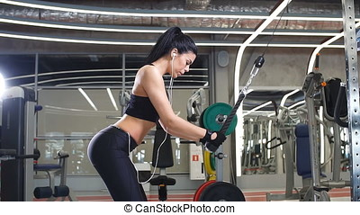 Woman doing exercise at crossover machine in gym - Rear view...