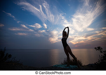 Woman doing exercise on a background of  beautiful sunset.