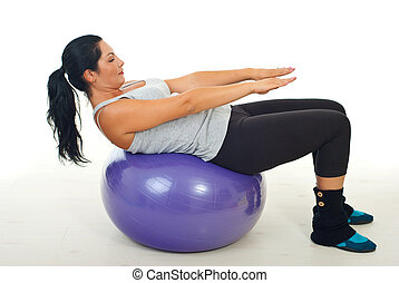 Woman doing exercise on pilates ball