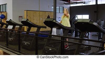 Woman doing exercise on treadmill in fitness studio 4k
