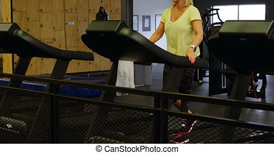 Woman doing exercise on treadmill in fitness studio 4k -...