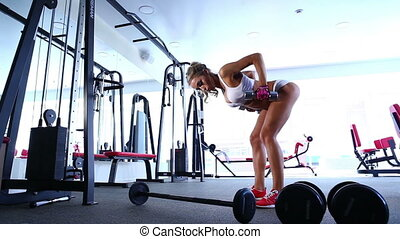 Woman doing exercise with barbell in the gym.