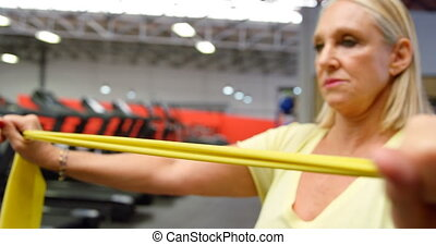 Woman doing exercise with resistance band 4k - Woman doing...