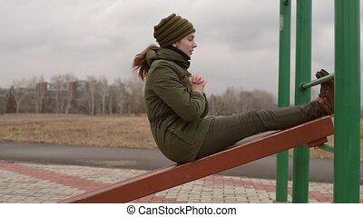 Woman doing exercise - Woman exercising abs outdoors in the...