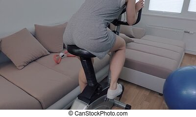 Woman doing exercises for butt on stationary bicycle