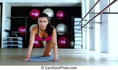 Woman doing exercises on mat in gym. Dolly shot