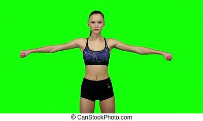 Woman doing exercises with dumbbells. Green screen