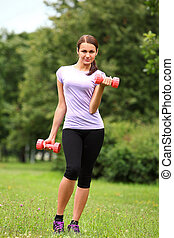 Woman doing exercises with dumbbells in the park