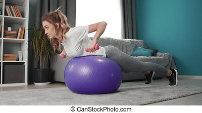 Woman doing exercises with dumbbells on fitness ball