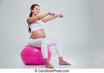 Woman doing exercises with dumbbells on a fitness ball
