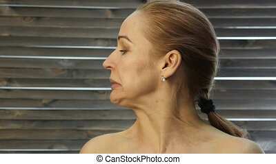 woman doing face fitness, aging chang in the muscles of the face.