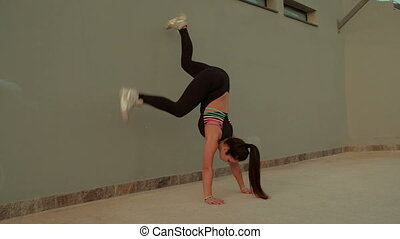 Woman doing fitness exercise Stand on hands of foot against wall