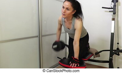 Woman doing fitness exercise with dumbbell for back muscles