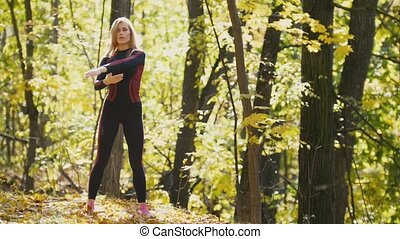 Woman doing fitness exercises outdoor. Female stretching her arms in autumn forest. Slim girl at outdoor workout