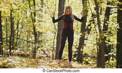 Woman doing fitness exercises outdoor. Female stretching her elbows in autumn forest. Slim girl at outdoor workout