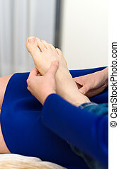 Woman doing foot massage to man at home.