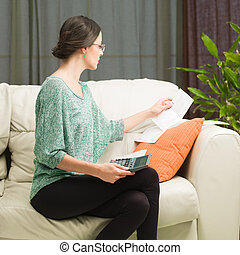 woman doing her accounts at home