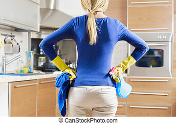 woman doing housekeeping - rear view of woman with yellow...