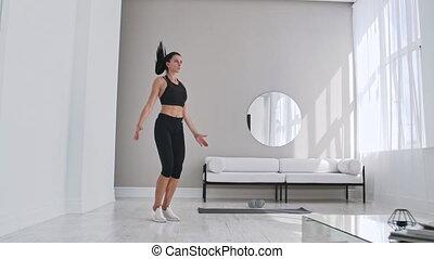 Woman doing jumping jacks at home. Sportswoman doing jumping jacks exercise at home