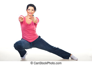 Woman doing lateral lunge and standing with hands...