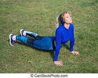 Woman doing lawn exercises and stretching on the grass outdoor in a park and listening music.