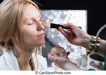 Woman doing make-up of the bride