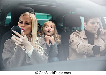 Woman doing makeup look at mirror sitting in car - Picture...