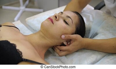 Woman doing neck massage at the reception of the chiropractor. Men's hands do massage of the cervical spine to an attractive girl.