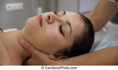 Woman doing neck massage at the reception of the chiropractor. Men's hands do massage of the cervical spine to an attractive girl. Face close-up. A grimace of pain.