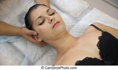 Woman doing neck massage at the reception of the chiropractor. Men's hands doing massage of the cervical spine. The girl in the bra lying on the couch during the procedure.