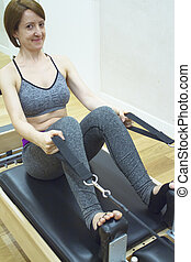 Woman doing pilates machine. Exercises to stretch the muscles