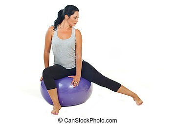 Woman doing pilates with mauve ball isolated on white...