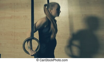 Woman doing pull-ups in a gym on gymnastic rings