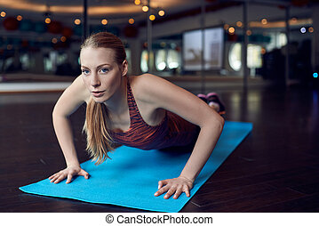 Woman doing push-up exercise in gym