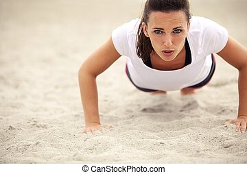 Woman Doing Push Up Exercise on the Beach - Push-ups fitness...