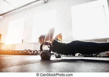 woman doing push-ups exercises on kettlebells. Cross fit training