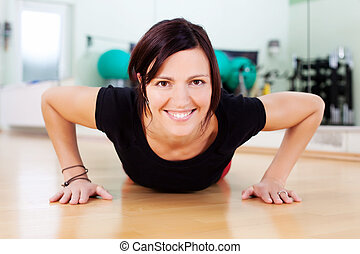 Woman doing push-ups in a gym