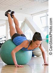 Woman Doing Push Ups On Swiss Ball At Gym